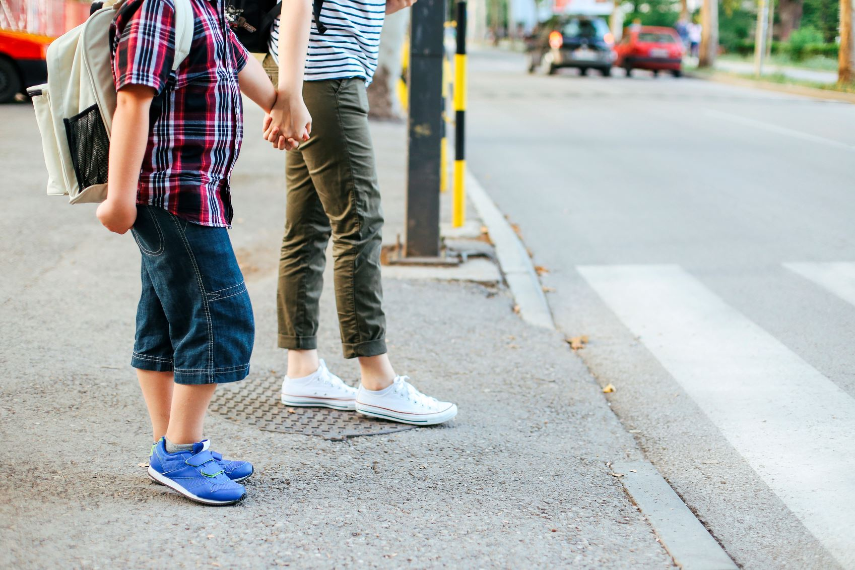 Two children holding hands waiting to cross the street